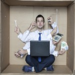Stressed busy man sitting in a cardboard box trying to do lots of tasks